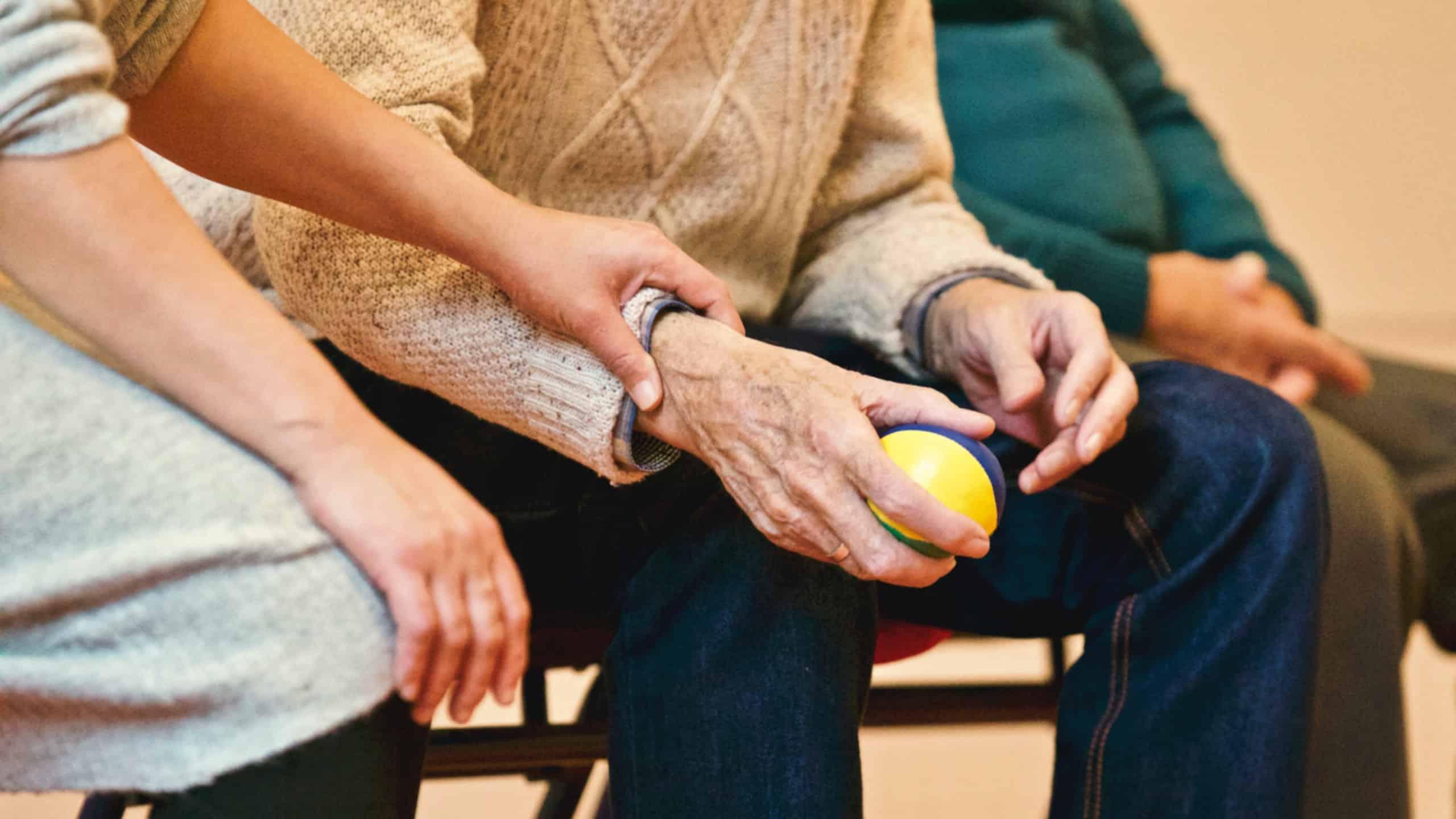 Photo d'une femme qui pose sa main sur la main d'un vieil homme